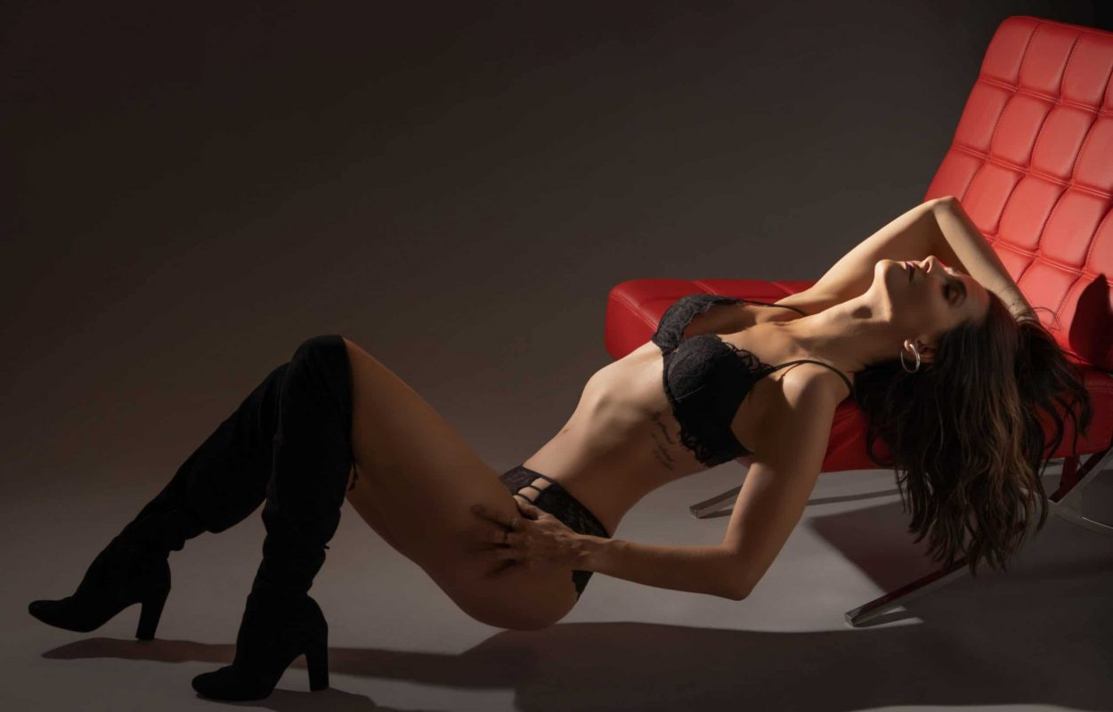 Lady in black lingerie leaning back on red couch.
