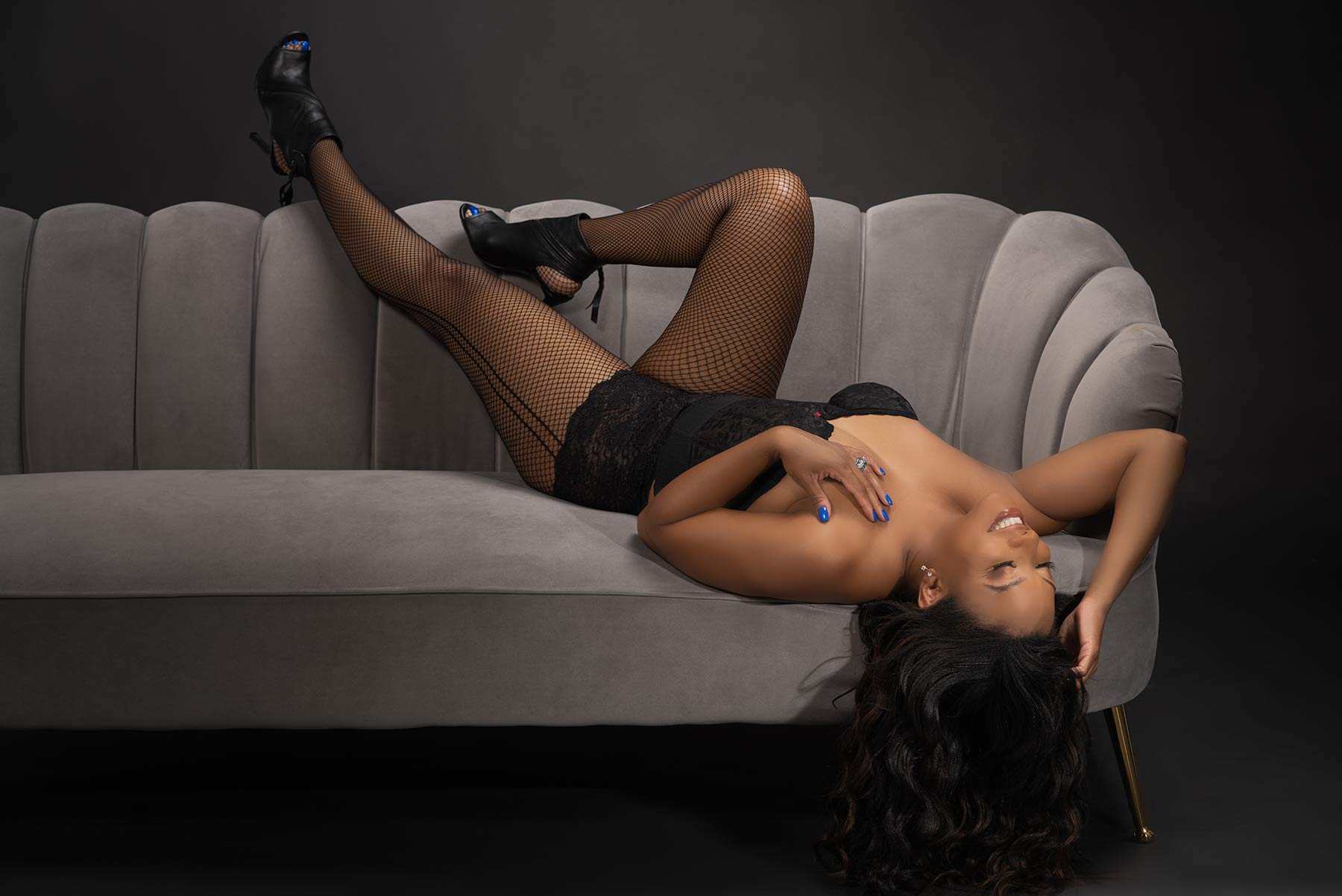 Woman laying on grey couch