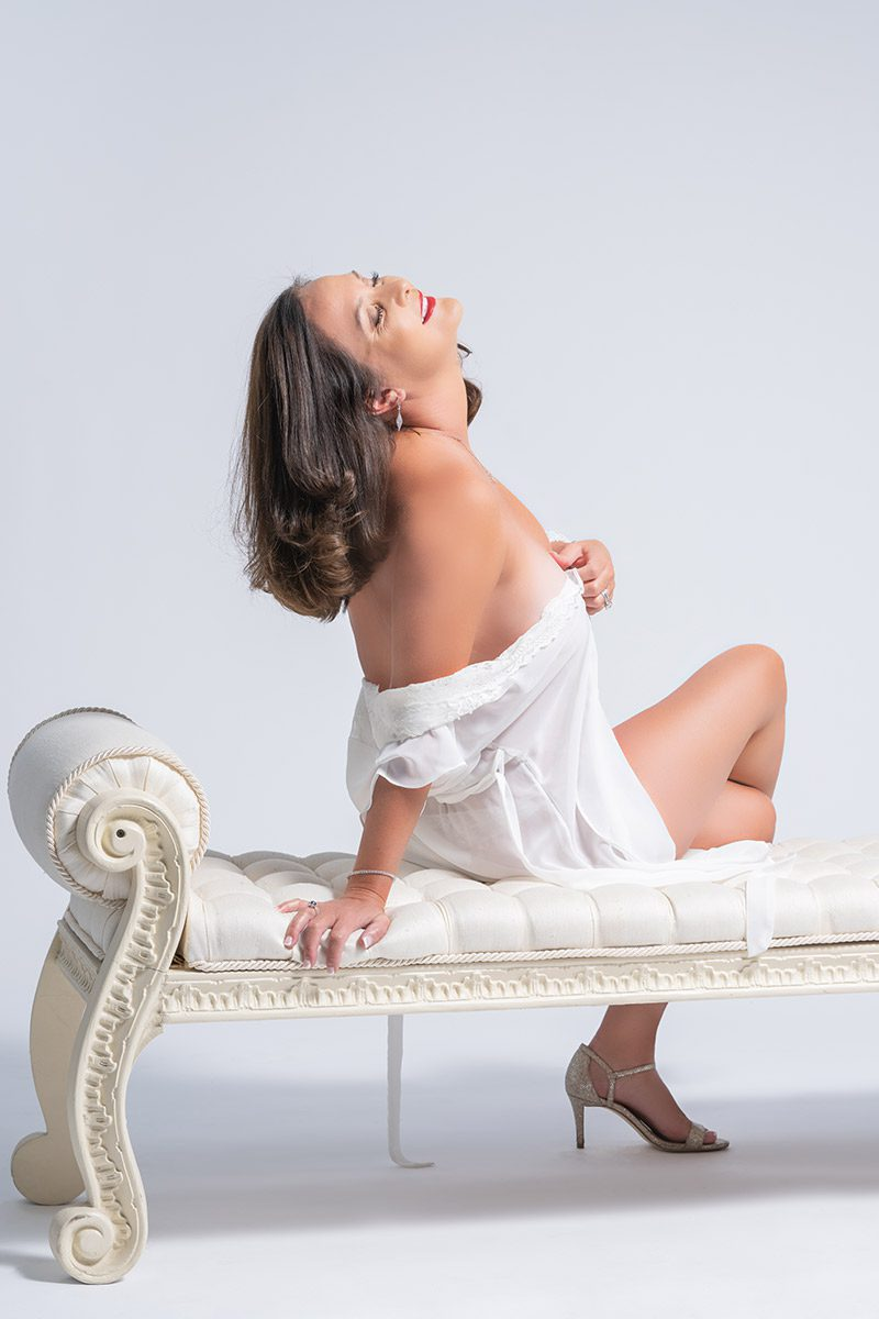 Woman posing on white chaise couch in white dress shirt for boudoir photoshoot