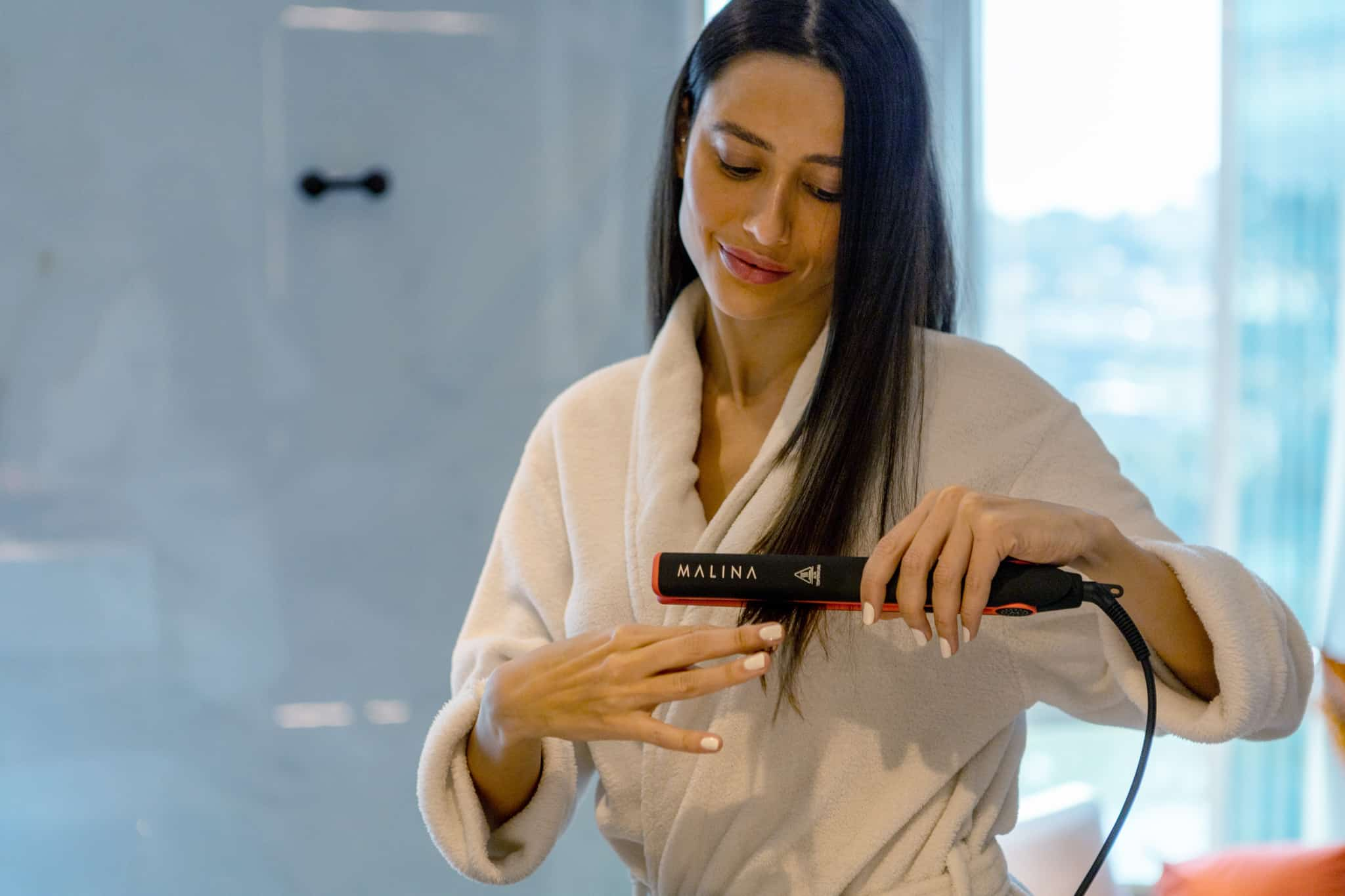 woman curling hair with a malina straightener