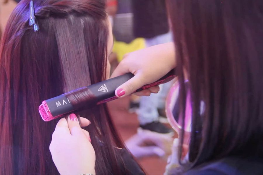 girl learning how to curl your hair with a straightener